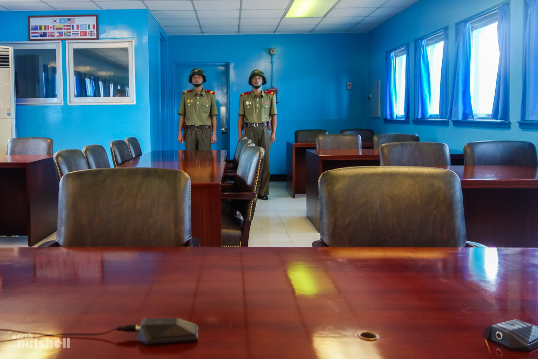 Conference room, seated at the negotiation table, facing the door to South Korea - guarded by two KPA soldiers.