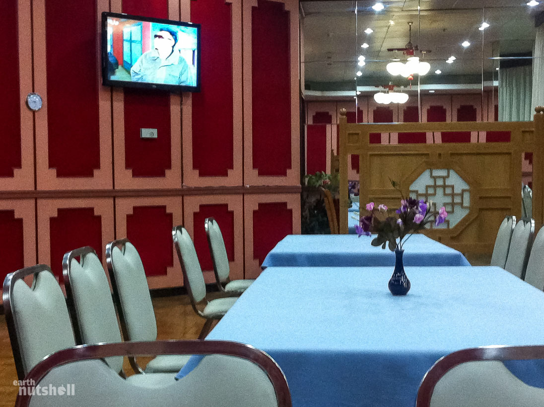 A dinner table laid out for one in an empty restaurant, three waitresses, ten plates of food and Kim Jong-Il.