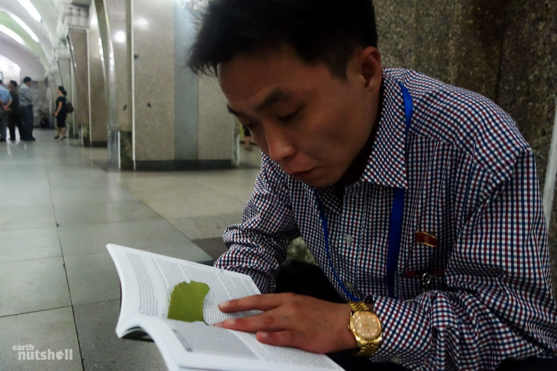 One of our North Korean guides reading a Lonely Planet guidebook on North Korea. The book was allowed, after being cleared by customs at Pyongyang Sunan International Airport. He was glued to it for hours, fascinating as to what we say about his beloved country.