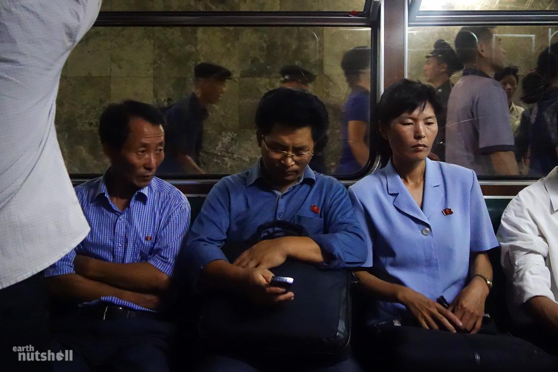 29-pyongyang-metro-commuters-mobile-phone-train